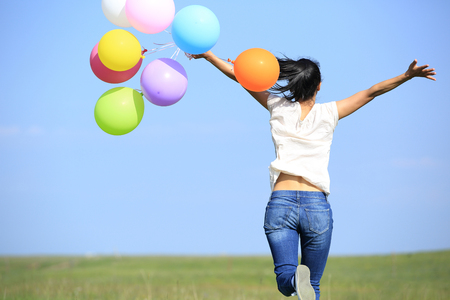 chinese lady: young asian woman running and jumping on green grassland with colored balloons Stock Photo
