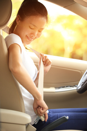 safe driving: woman driver buckle up the seat belt before driving car Stock Photo