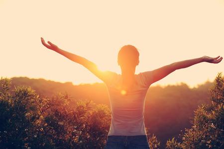 cielos abiertos: animando los brazos abiertos mujer en el pico de la montaña la salida del sol