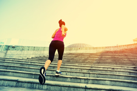 escalera: Runner atleta que corre en las escaleras. Aptitud de la mujer trotar entrenamiento concepto de bienestar.