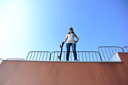 girl action: Skateboarder woman standing at skatepark.