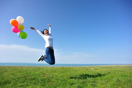실행 하 고 색깔의 풍선과 함께 녹색 목초지에 점프 젊은 아시아 여자