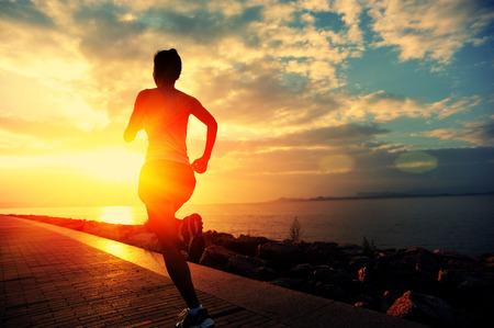 Runner atleta in esecuzione in riva al mare. fitness donna silhouette alba pareggiare allenamento concetto di benessere.
