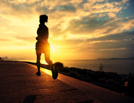 ser humano: Runner atleta que corre en la playa. Aptitud de la mujer silueta de la salida del sol para correr entrenamiento concepto de bienestar. Foto de archivo