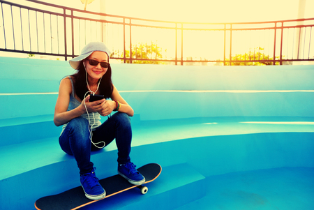hold: woman skateboarder sit on skatepark stairs listening music from smart phone mp3 player Stock Photo