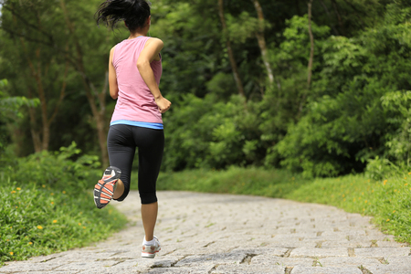 woman street: young fitness woman legs running at forest trail