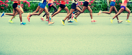 challenging: Marathon running race, people feet on city road Stock Photo