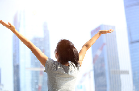 love life: cheering woman open arms at city