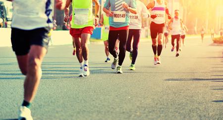 Maratón de carrera a pie, la gente los pies en el camino de ciudad
