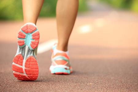 Junge Eignungsfrauen-Läuferbeine, die an der Schneise laufen Standard-Bild