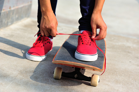 shoelace: young woman skateboarder tying shoelace