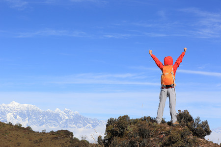 hiking: cheering young woman hiker open arms at mountain peak