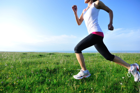 Runner athlete running on grass seaside. woman fitness jogging workout wellness concept. Banco de Imagens