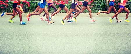 vida sana: Maratón de carrera a pie, la gente los pies en el camino de ciudad