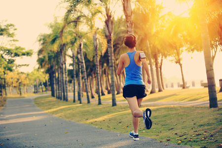 Fitness woman running at tropical park.