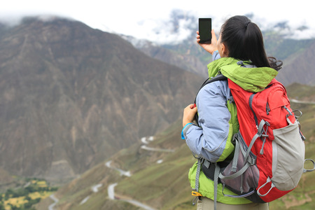 trekker: woman photographer taking photo at mountain peak in tibet,china