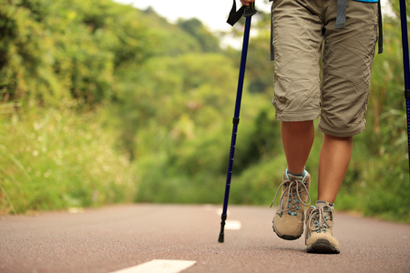 walking pole: Young fitness woman legs walking on forest trail.