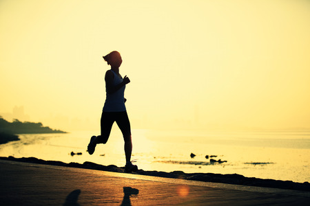 bewegung menschen: Runner Athlet am Meer laufen. Frau Fitness Silhouette Sonnenaufgang Jogging Training Wellness-Konzept. Lizenzfreie Bilder