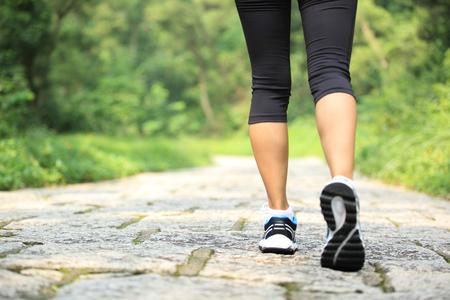Młoda kobieta fitness spacery w leśnym szlakiem