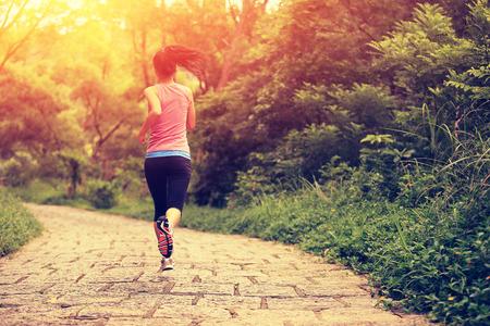 林道を走っている若いフィットネス女性
