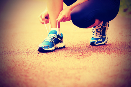 woman tie: young woman runner tying shoelaces