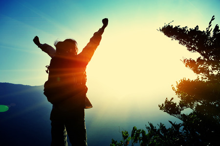 arm: cheering woman hiker open arms at mountain peak Stock Photo