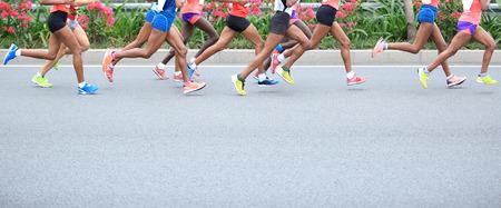 gimnasio mujeres: Maratón de carrera a pie, la gente los pies en el camino de ciudad