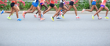 women legs: Marathon running race, people feet on city road Stock Photo