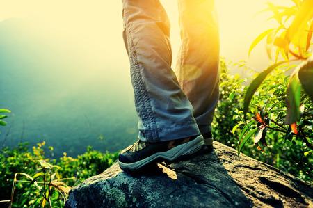 womna: woman hiker legs climbing on sunrise mountain peak rock