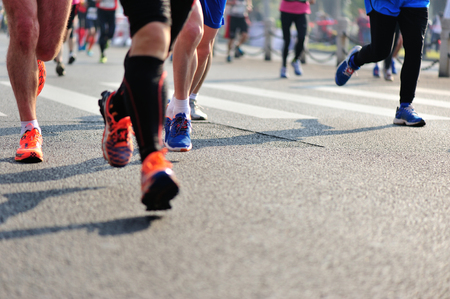 crowded space: Marathon running race, people feet on city road Stock Photo