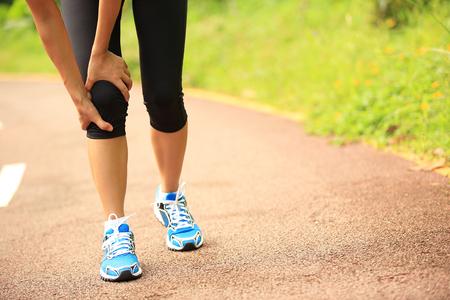sports injury: woman runner hold her sports injured knee Stock Photo