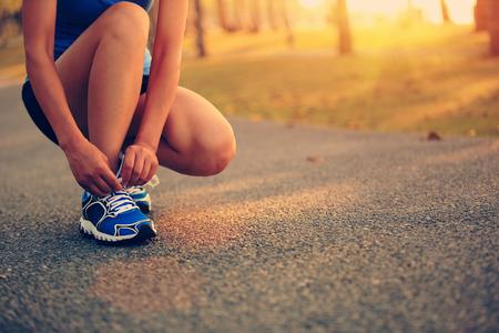 jonge vrouw runner koppelverkoop schoenveters Stockfoto