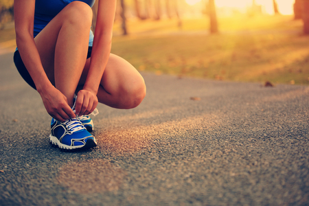 sport wear: young woman runner tying shoelaces