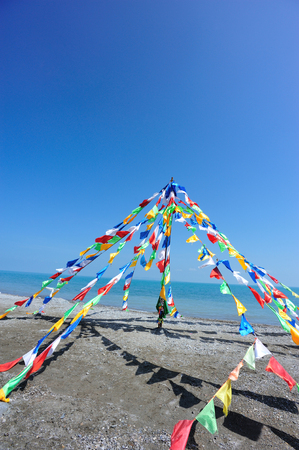 sutras: buddhist tibetan prayer flags waving in the wind against blue sky