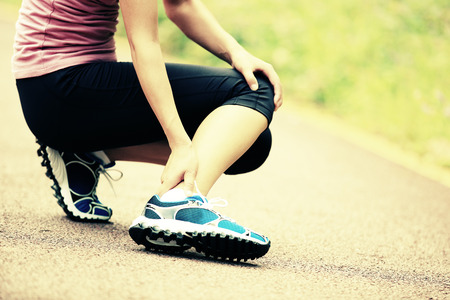 leg calf injury: woman runner hold her twisted ankle