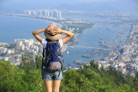 女性ハイカー スタンド山頂景色眺めて