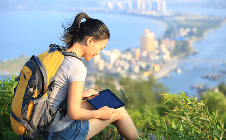smiling girl: young asian woman hiker use digital tablet seaside mountain peak