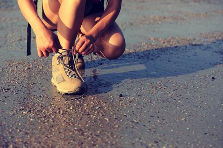 shoelace: young asian woman hiker tying shoelace on sunrise beach