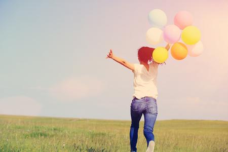 giovane donna asiatica in esecuzione e saltando su prati verdi con palloncini colorati