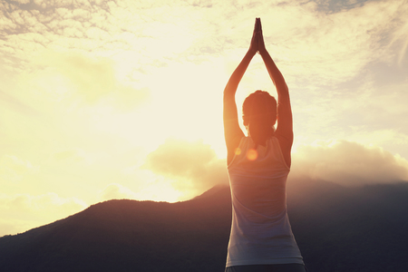 yoga meditation: young yoga woman at sunrise mountain peak Stock Photo