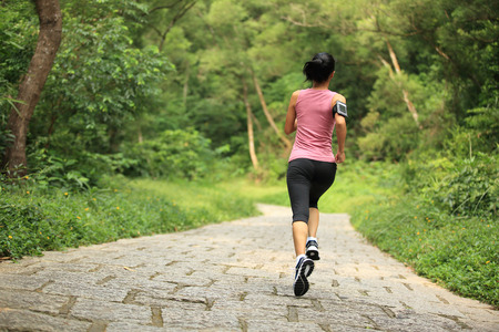 forest trail: young fitness woman running at forest trail