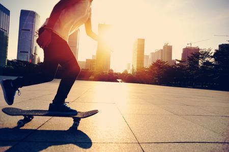 city of sunrise: woman skateboarder legs skateboarding at sunrise city Stock Photo