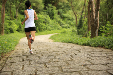 back roads: young fitness woman running at forest trail