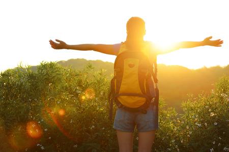 山のピークに立つ日の出に感謝して女性ハイカー オープンアームズ 写真素材