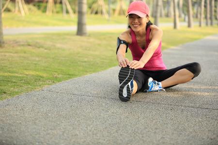 vida sana: Corredor de la mujer que estira las piernas al aire libre