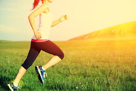 lifestyle: Biegacz sportowiec działa na trawie nad morzem. kobieta fitness sunrisesunset jogging trening wellness koncepcji.