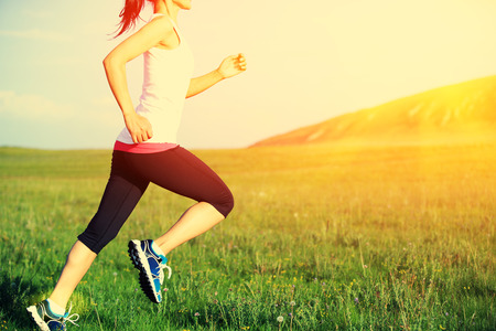 jogging: Runner athlete running on grass seaside. woman fitness sunrisesunset jogging workout wellness concept. Stock Photo