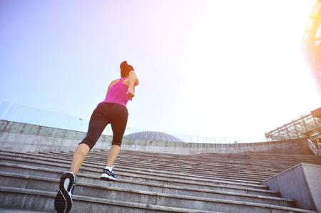 escalando: Runner atleta que corre en las escaleras. Aptitud de la mujer trotar entrenamiento concepto de bienestar.