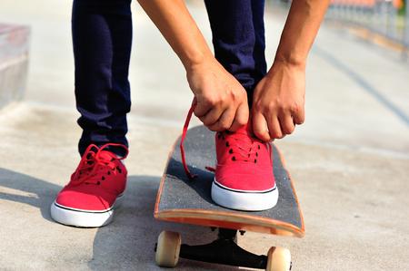 shoelace: oung woman skateboarder tying shoelace