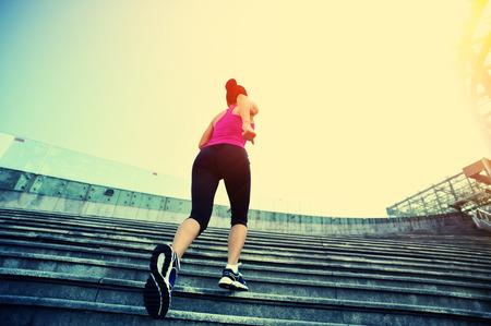 gente exitosa: Runner atleta que corre en las escaleras. Aptitud de la mujer trotar entrenamiento concepto de bienestar.